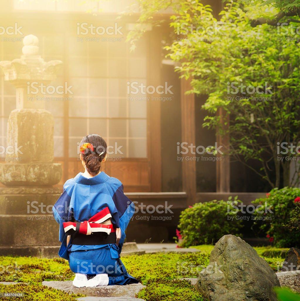 Rear view Japanese woman praying beam of light square version stock photo