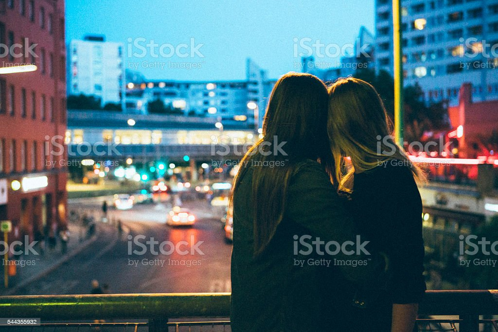 rear view, loving women couple looking looking at city lights stock photo