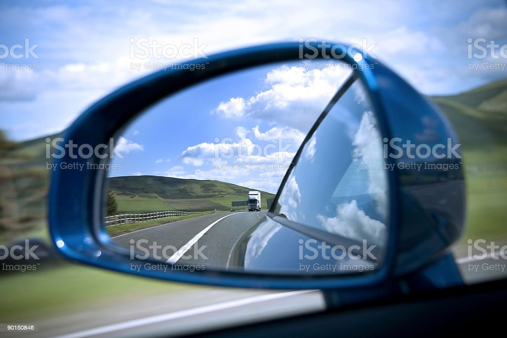 Rear view mirror on road showing semi truck stock photo