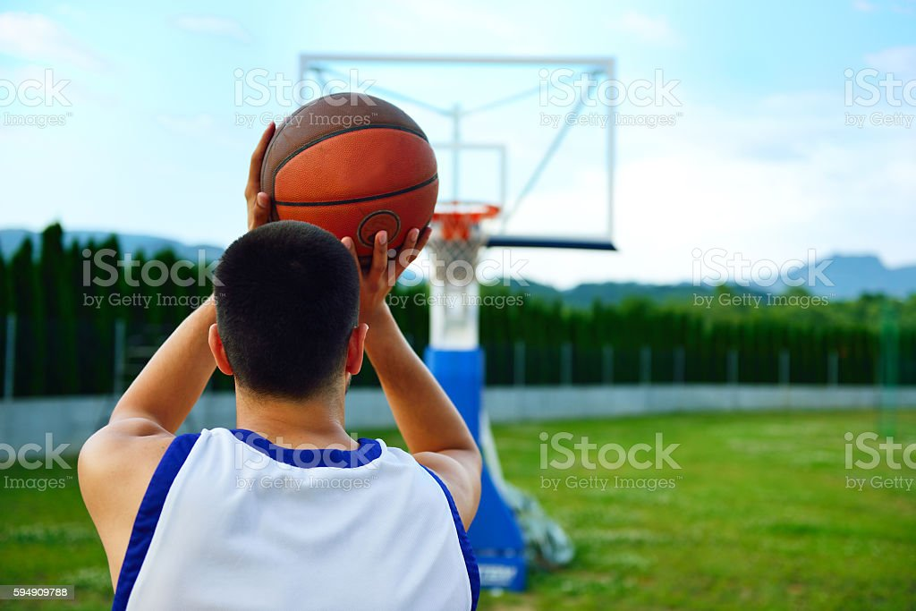 Rear view of a basketball player, shooting at basket outdoor stock photo