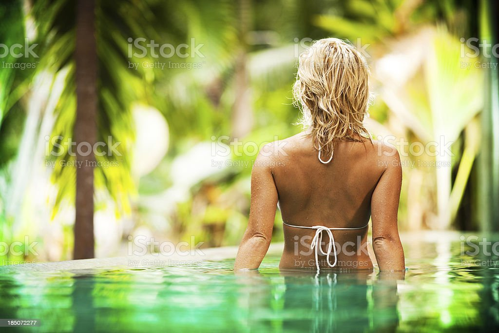 Rear view of a blonde woman enjoying in swimming pool. royalty-free stock photo