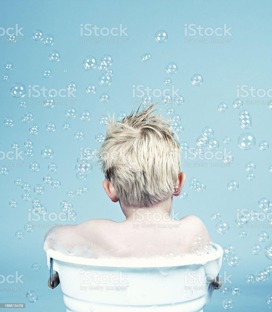 Rear view of a boy sitting in bathtub royalty-free stock photo