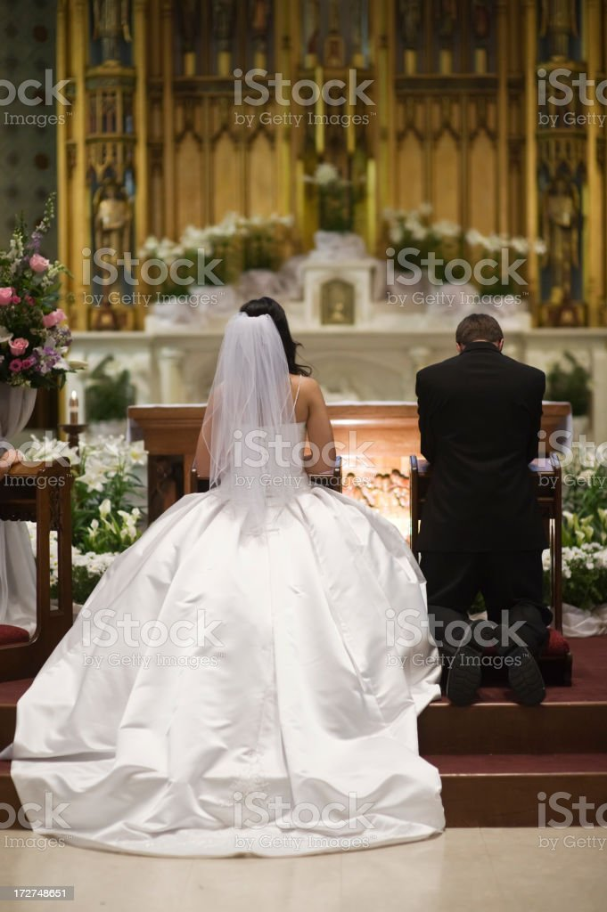 Rear view of a bride and groom kneeling at altar at wedding royalty-free stock photo