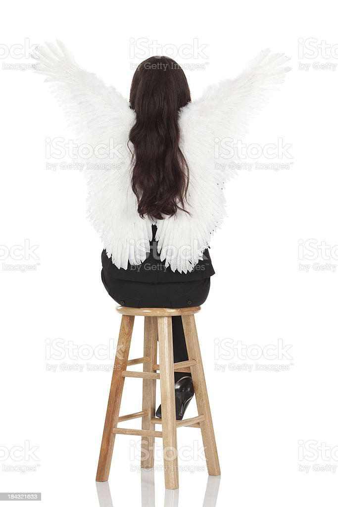 Rear view of a business angel sitting on stool stock photo