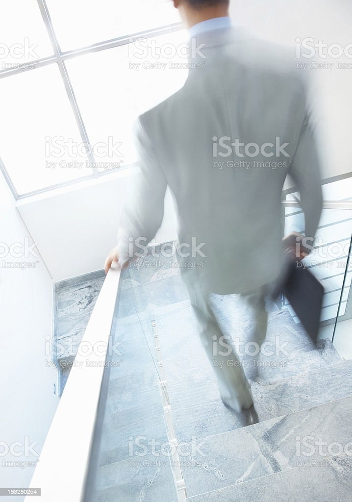 Rear view of a business man walking down the stairs royalty-free stock photo