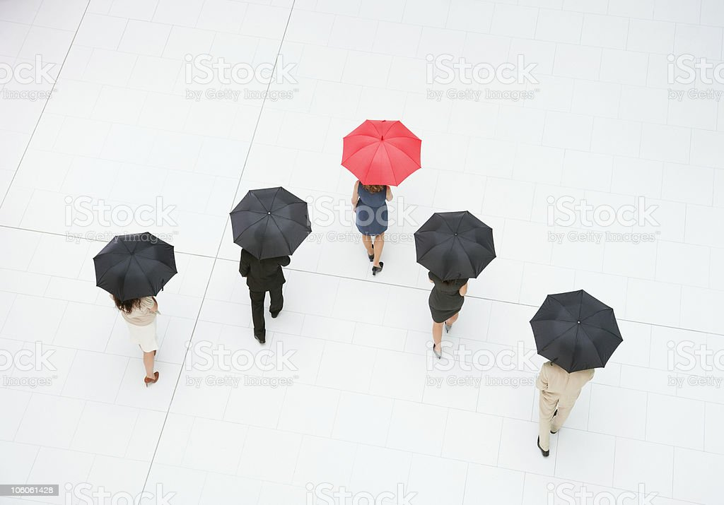 Rear view of a business people walking with umbrellas royalty-free stock photo