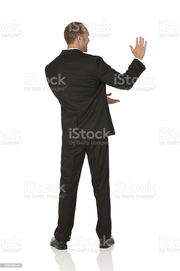 Rear view of a businessman gesturing stock photo