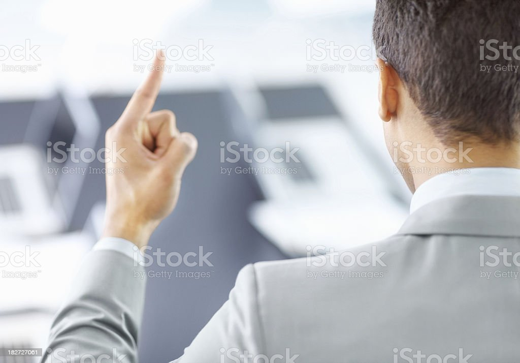 Rear view of a businessman holding up index finger royalty-free stock photo