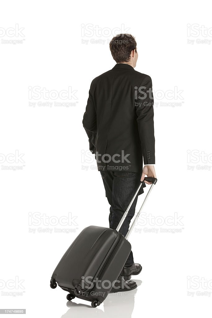 Rear view of a businessman pulling his trolley bag royalty-free stock photo