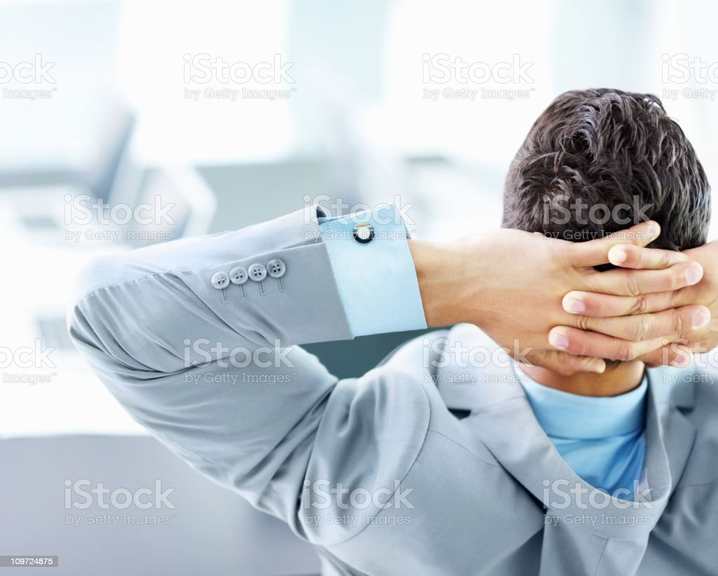Rear view of a businessman relaxing in the office stock photo