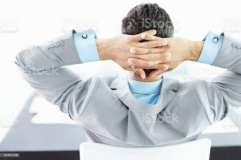 Rear view of a businessman sitting with hands behind head royalty-free stock photo