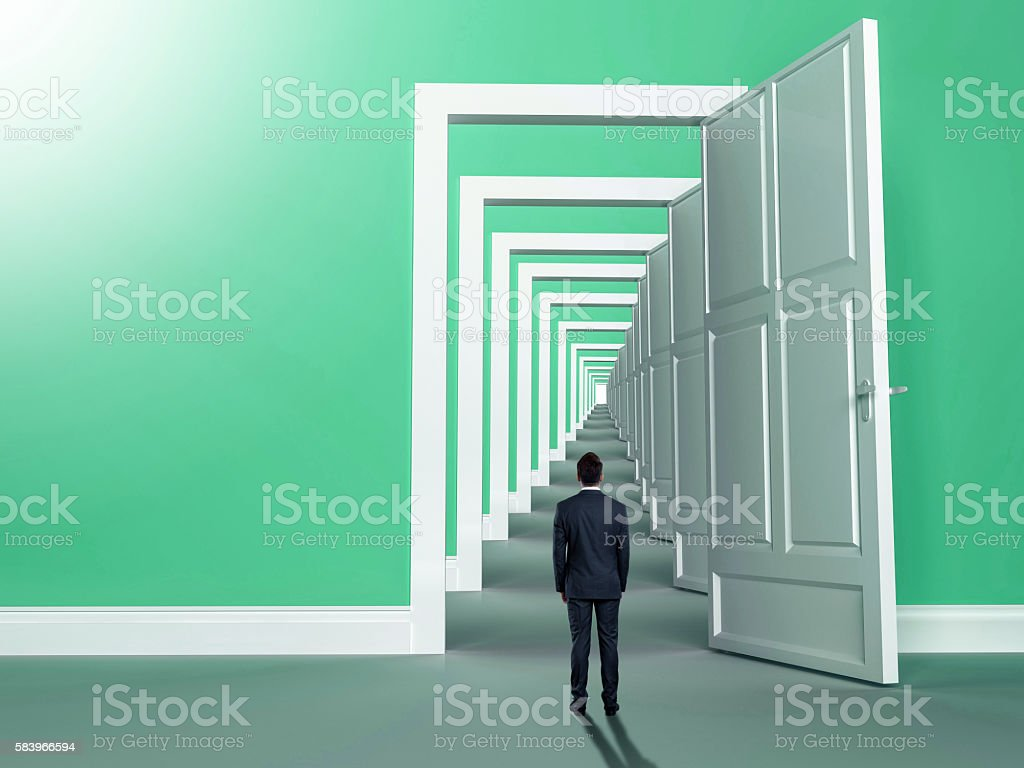 Rear view of a businessman standing in front of door stock photo