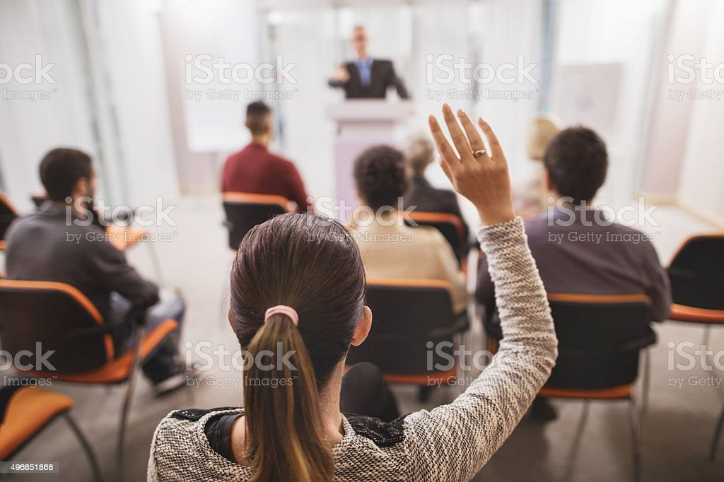 Rear view of a businesswoman raising her hand on seminar. stock photo