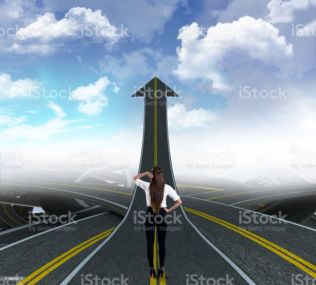 Rear view of a businesswoman standing on way to success stock photo