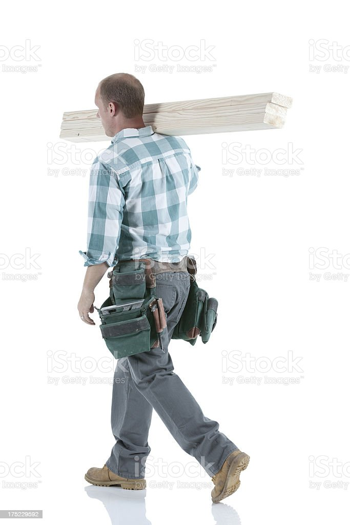 Rear view of a carpenter carrying logs royalty-free stock photo