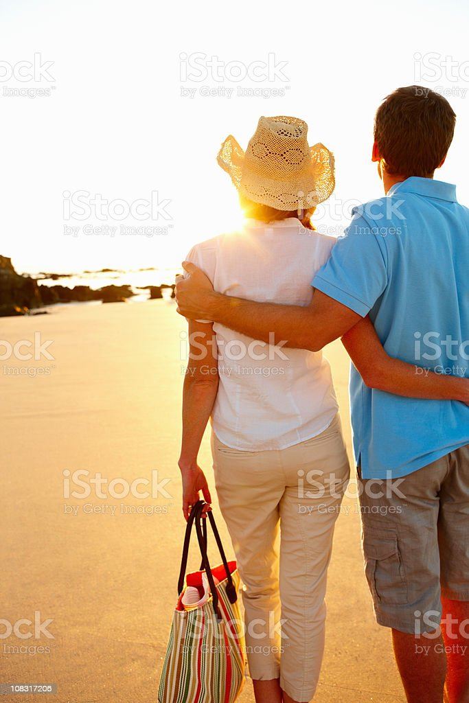 Rear view of a couple facing the sunset at beach royalty-free stock photo
