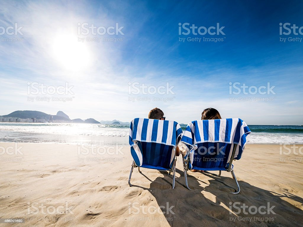 Rear view of a couple in deck chairs at beach. stock photo