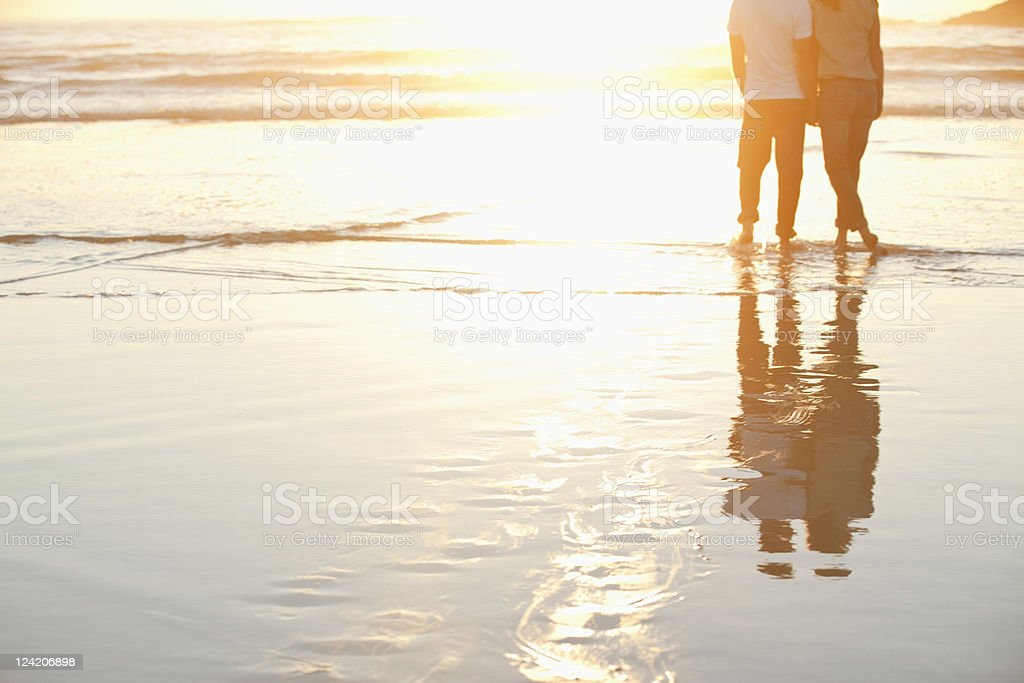Rear view of a couple standing together on beach at sunset stock photo