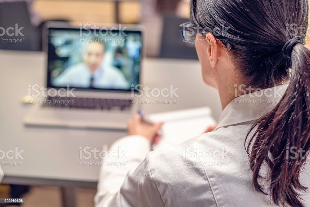 Rear view of a doctor having a video conference stock photo