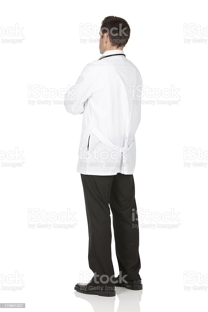 Rear view of a doctor with arms crossed against white stock photo