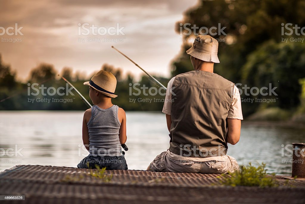 Rear view of a father and son freshwater fishing. stock photo