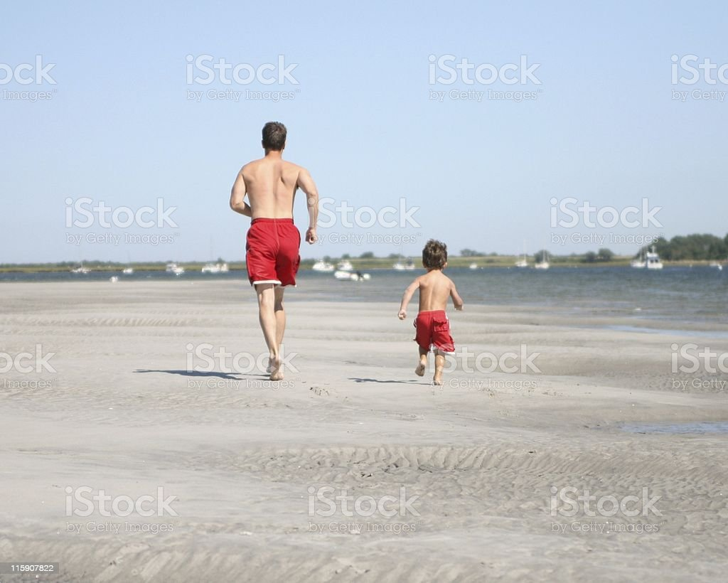 Rear view of a father and son in red shorts running on beach royalty-free stock photo
