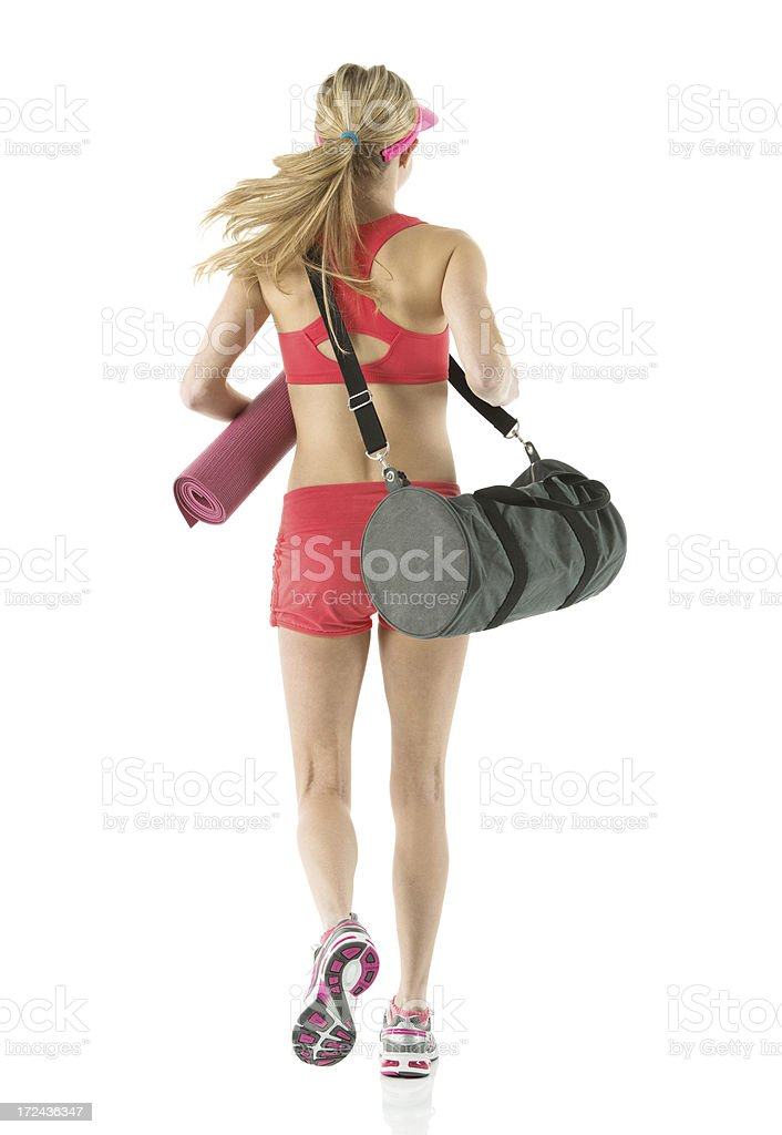 Rear view of a female athlete carrying exercise mat royalty-free stock photo