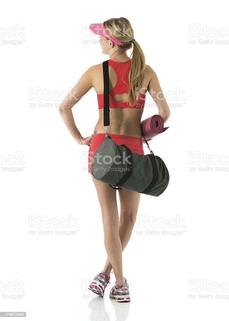 Rear view of a female athlete standing with exercise mat royalty-free stock photo