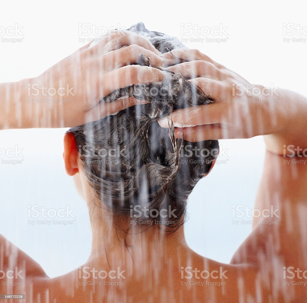 Rear view of a female shampooing her hair in shower stock photo