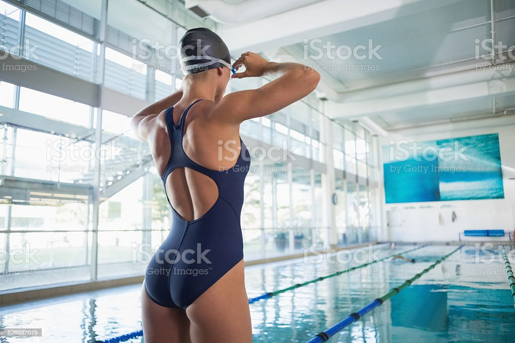 Rear view of a fit swimmer by pool stock photo