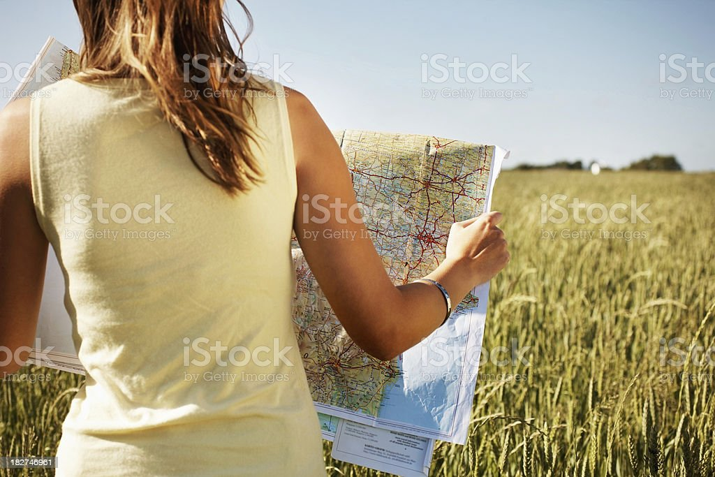 Rear view of a lady with road map in field stock photo