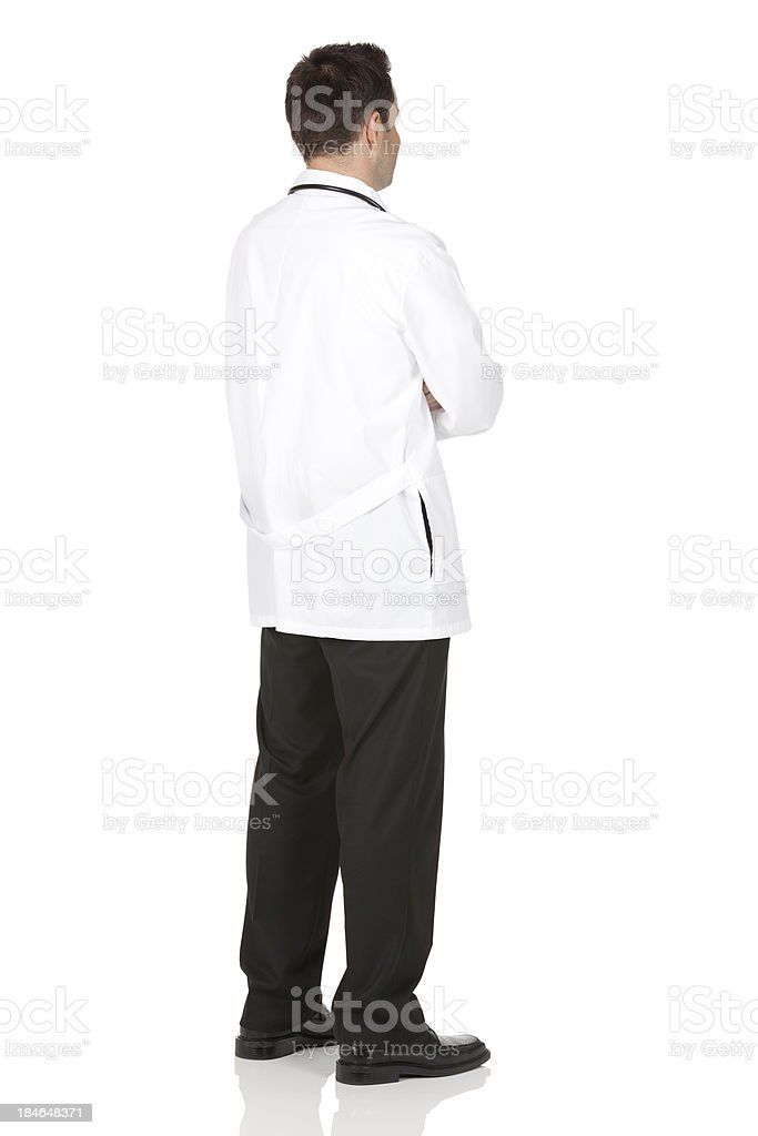 Rear view of a male doctor standing with arms crossed stock photo