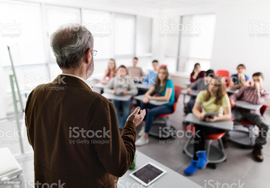Rear view of a male teacher giving a lecture. stock photo
