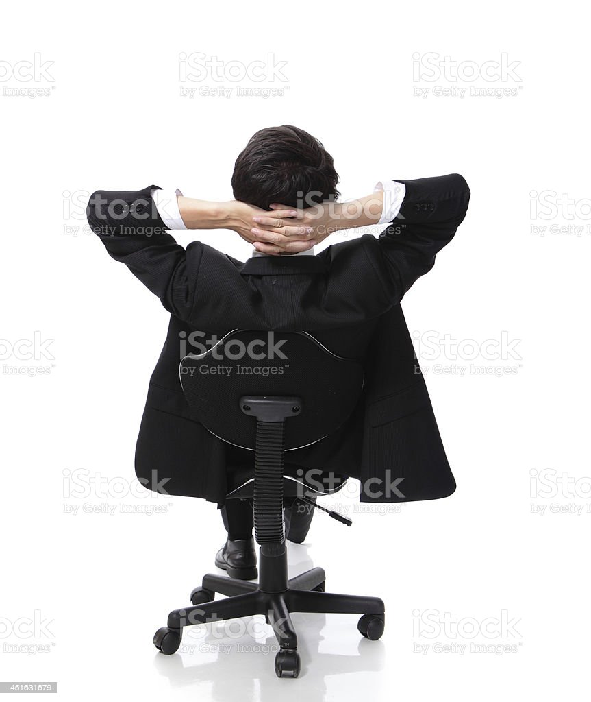 Rear view of a man in a suit relaxing on a chair stock photo