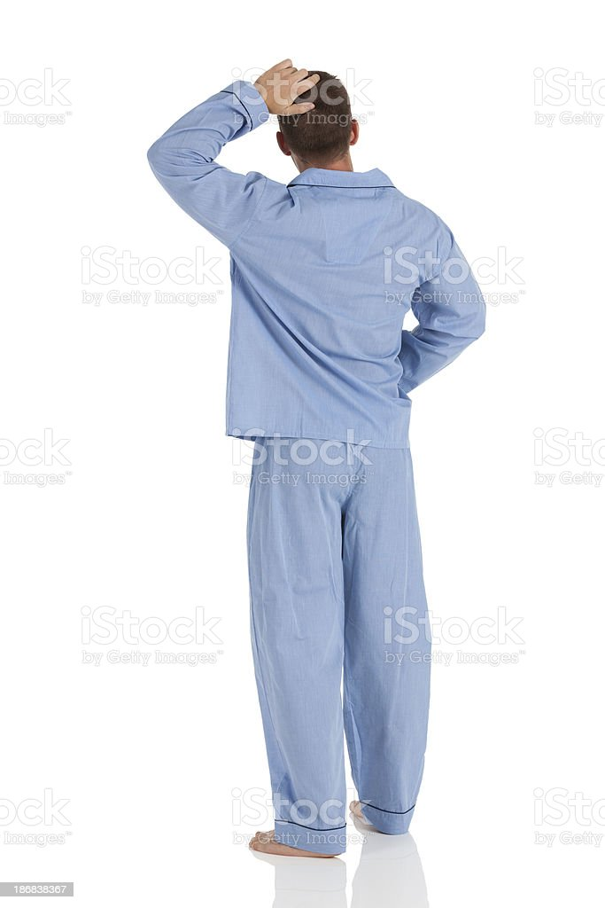 Rear view of a man in pajamas scratching head stock photo