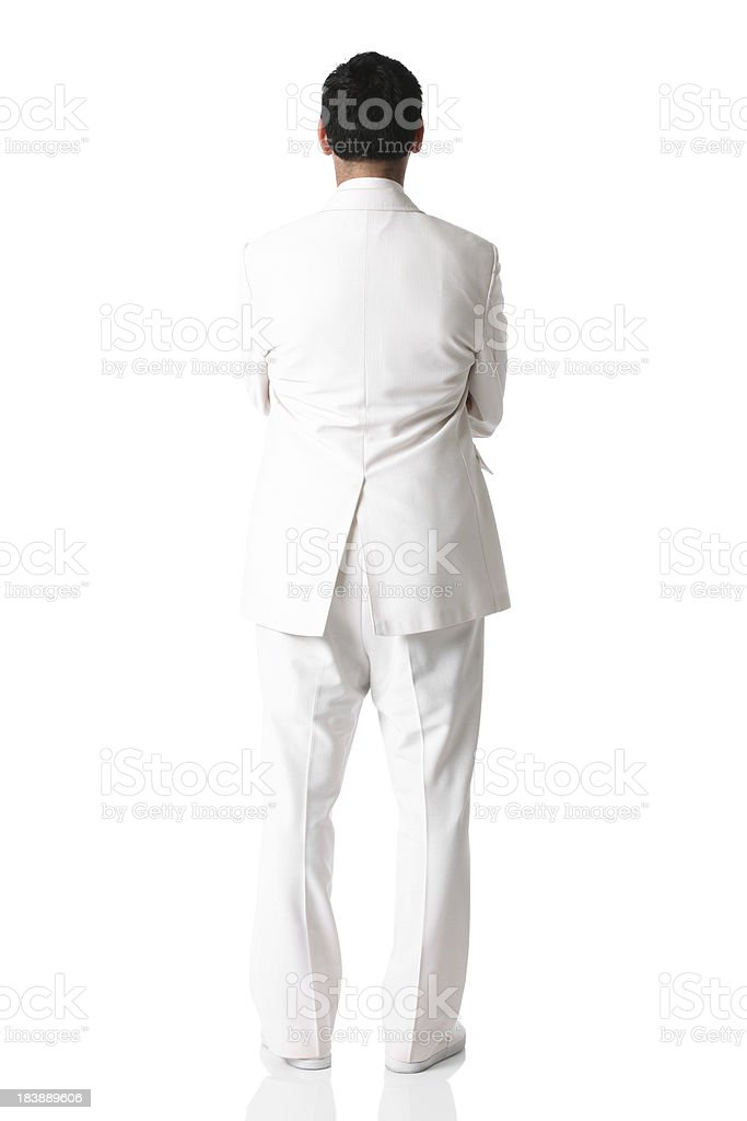Rear view of a man in white suit standing with arms stock photo