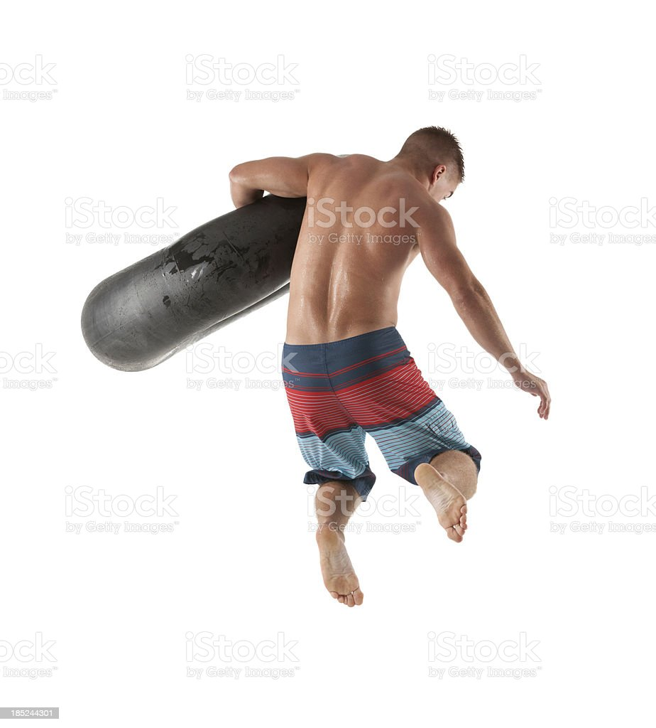 Rear view of a man jumping with inner tube royalty-free stock photo
