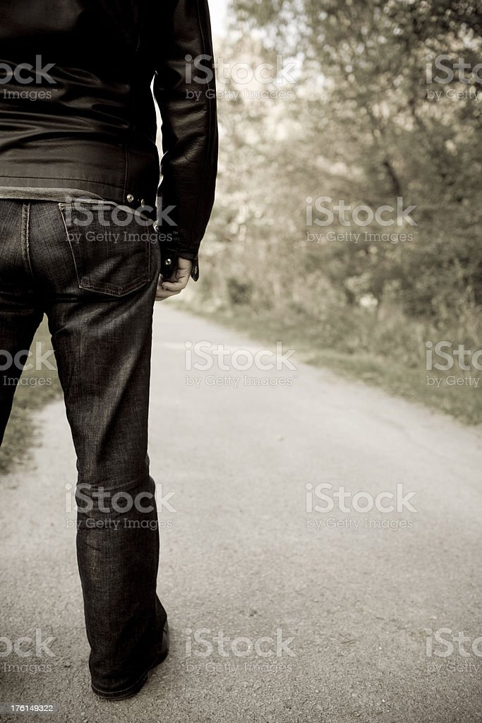 Rear view of a man looking down an empty road beside trees. royalty-free stock photo