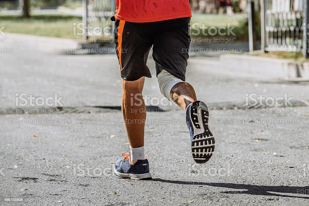 rear view of a man running through streets of city royalty-free 스톡 사진