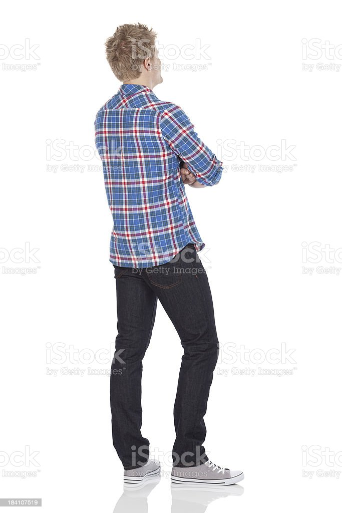 Rear view of a man standing with arms crossed stock photo