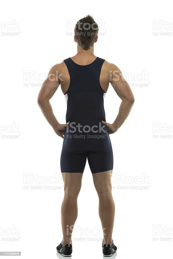 Rear view of a man standing with hands on hips stock photo