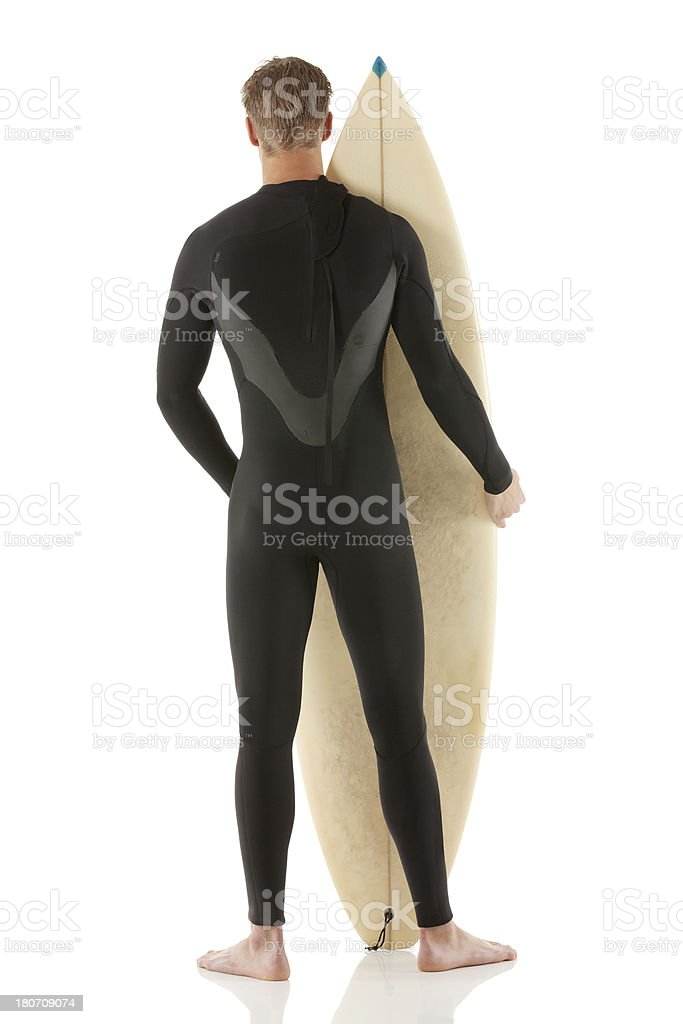 Rear view of a man standing with surfboard royalty-free stock photo