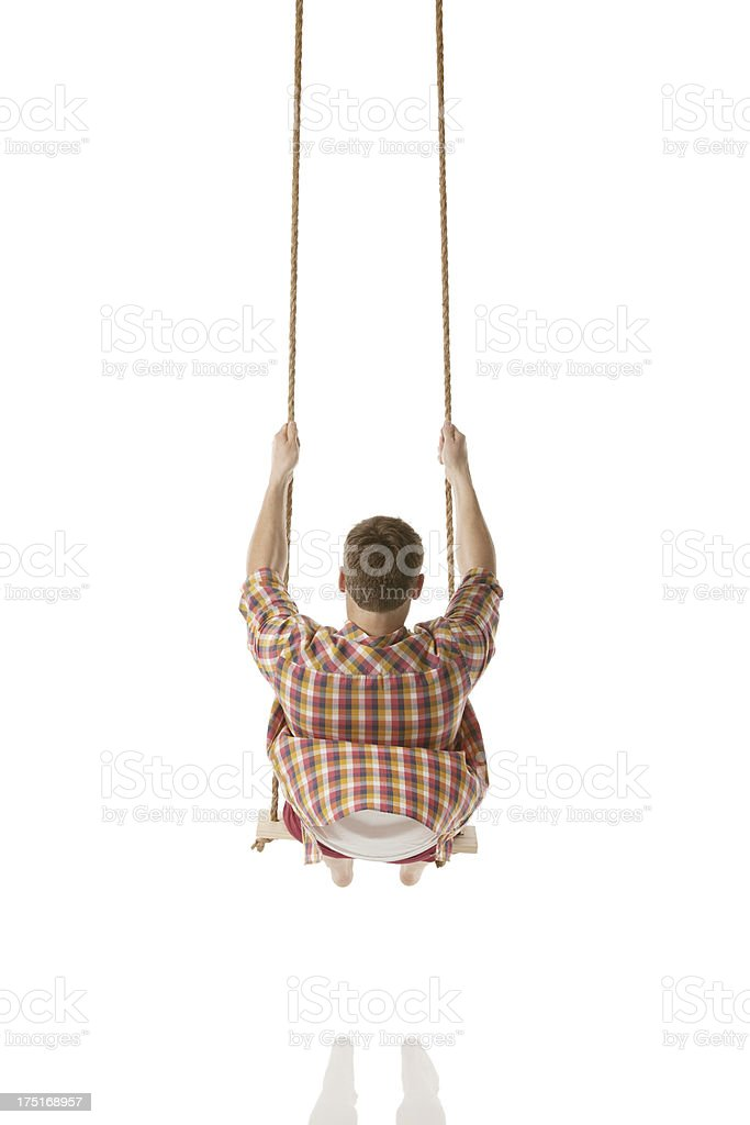 Rear view of a man swinging on rope swing royalty-free stock photo