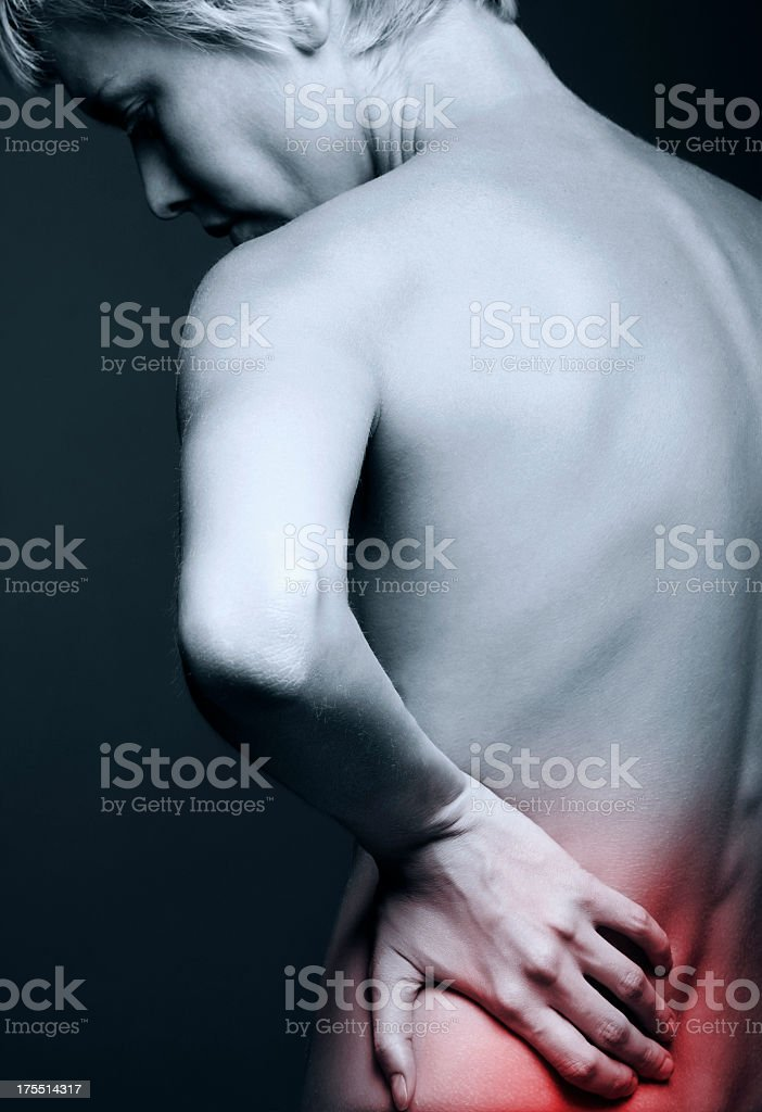 Rear view of a naked woman with back pain highlighted in red royalty-free stock photo