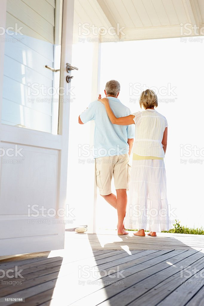 Rear view of a romantic couple at beach house royalty-free stock photo