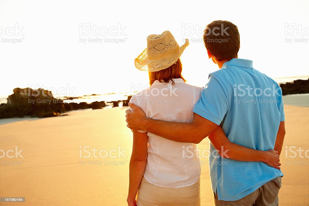 Rear view of a romantic couple enjoying the sunset royalty-free stock photo