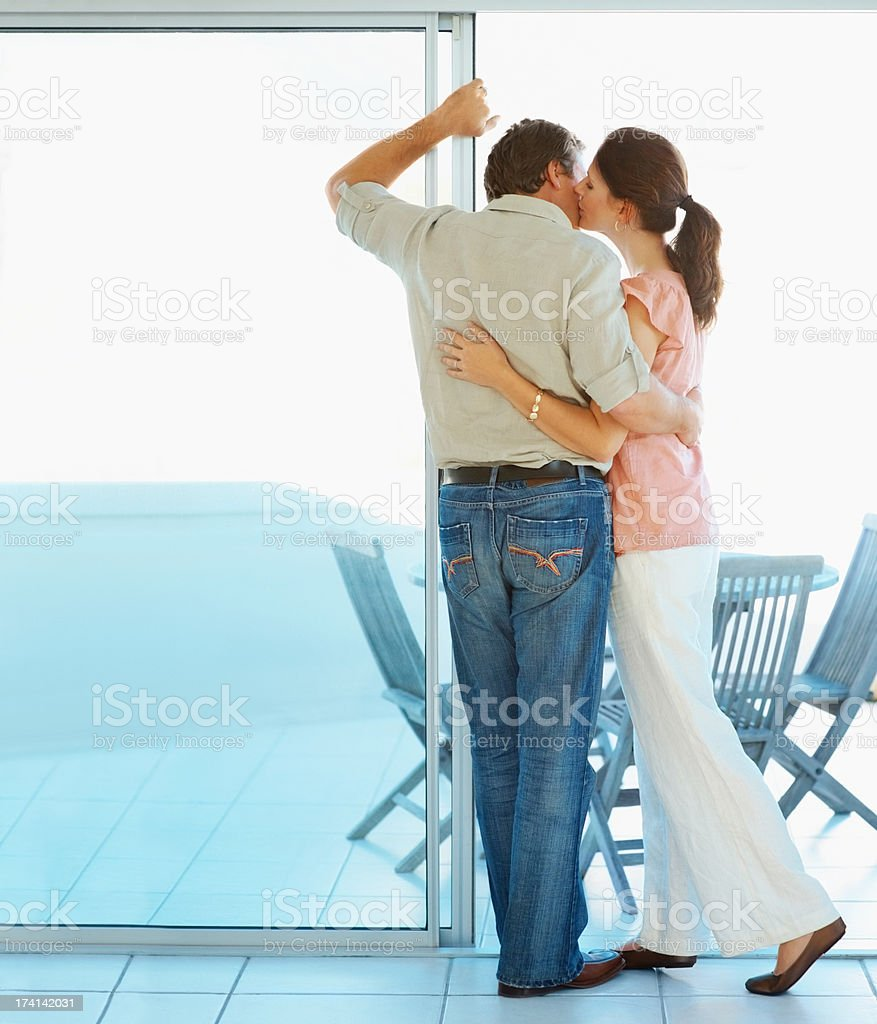 Rear view of a romantic couple kissing by the porch stock photo
