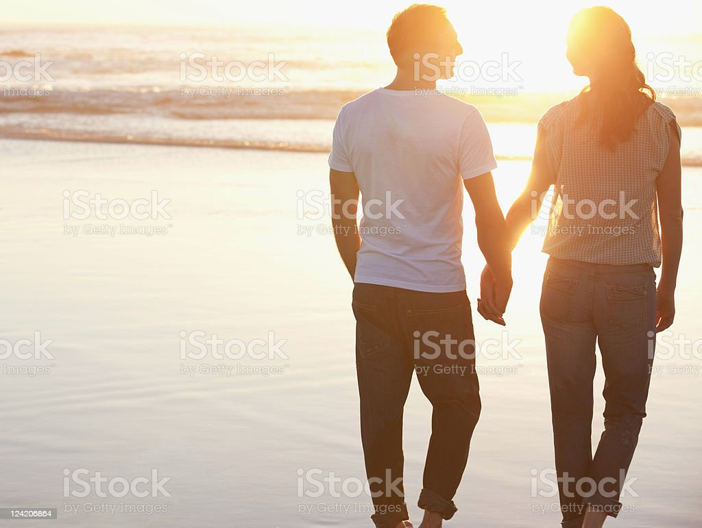 Rear view of a romantic couple walking at beach holding hands royalty-free stock photo