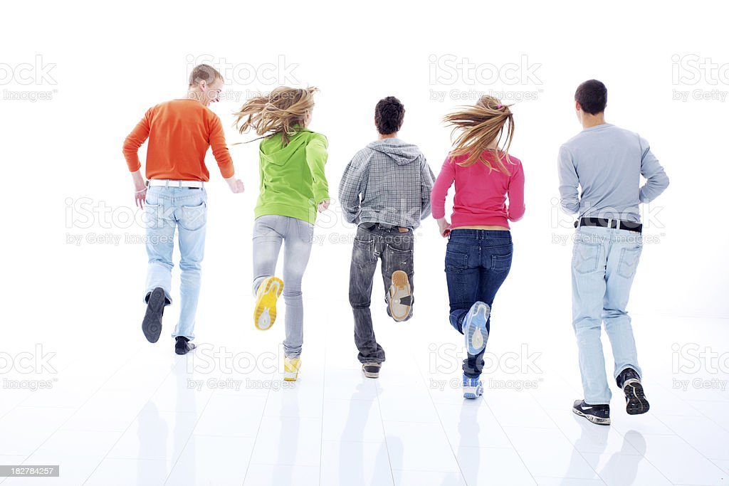 Rear view of a running teenagers, dressed colorful. royalty-free stock photo