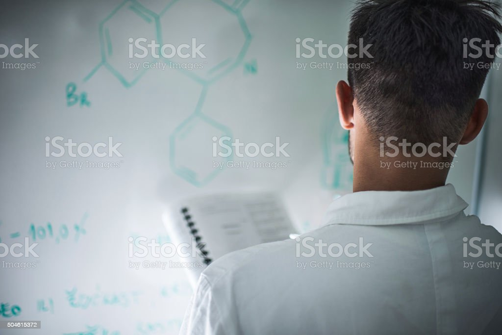 Rear view of a scientist analyzing molecular structure on whiteboard. stock photo